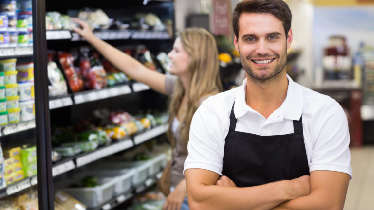 Portrait of a handsome seller with arm crossed at supermarket